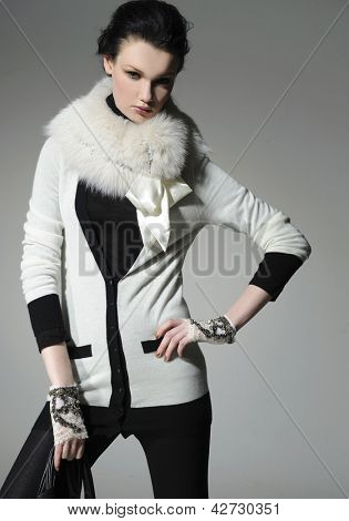 Stylish model in fur coat in white coat posing on gray background