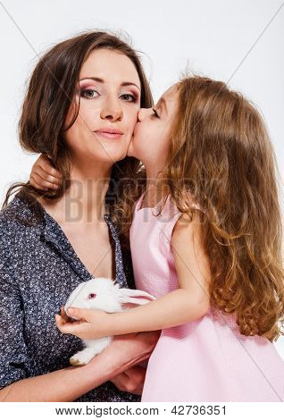Cute little girl with long hair kissing her mom
