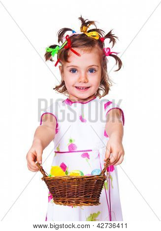 Smiling preschool girl holding wicker basket with Easter decoration