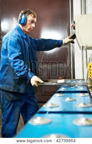 worker at manufacture workshop operating guillotine shears machine