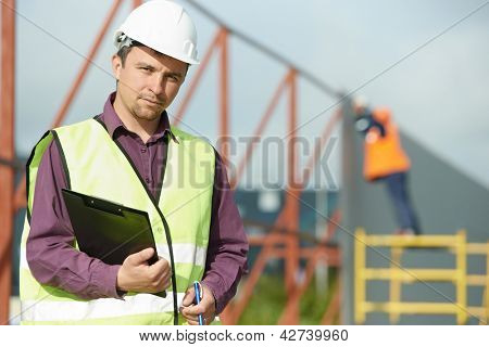 site manager builder worker in uniform and safety protective equipment at construction site in front of metal construction frames