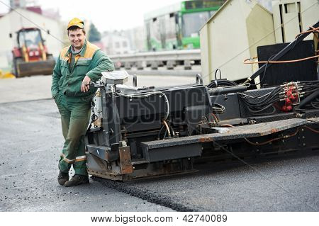 happy road construction worker near asphalt paver machine