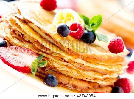 Pancake. Crepes With Berries. Pancakes stack with Strawberry, Raspberry, Blueberry and Syrup isolated on a White Background