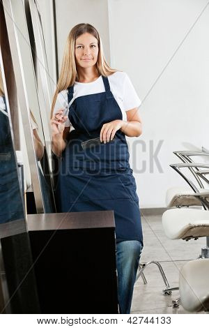 Environmental Portrait of female hairstylist with scissors and comb in beauty parlor