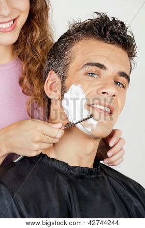 Portrait of happy man getting a shave from barber at salon