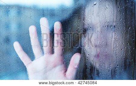 Melancholy And Sad Young  Woman  At The Window In The Rain