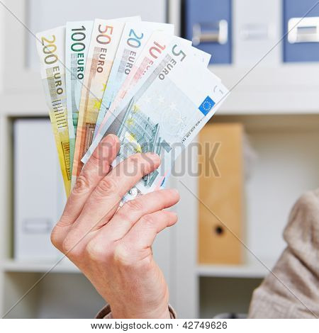 Hand in office holding fan of different Euro bills