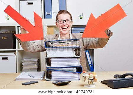 Happy business woman in office pointing arrows to stack of files