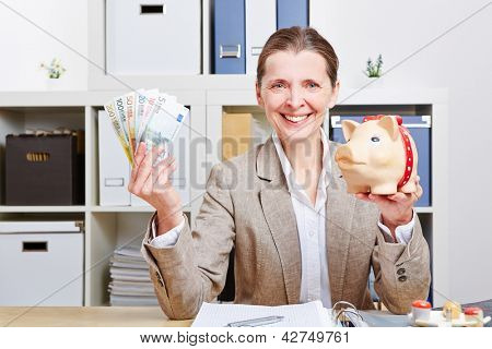 Happy elderly business woman with piggy bank and Euro money in her office