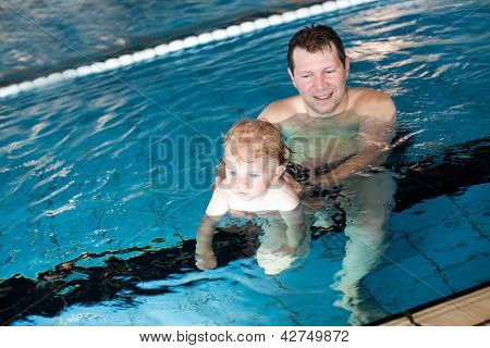 Father And Baby Boy Swimming In A Swimming Pool
