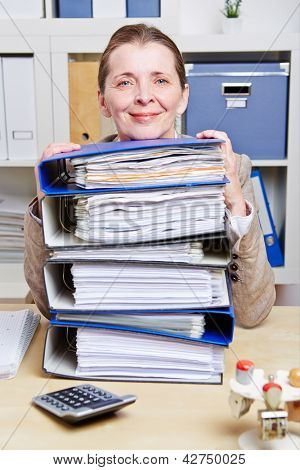 Smiling senior business woman with files on her desk in her office