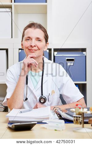 Portrait of happy senior female doctor in her office