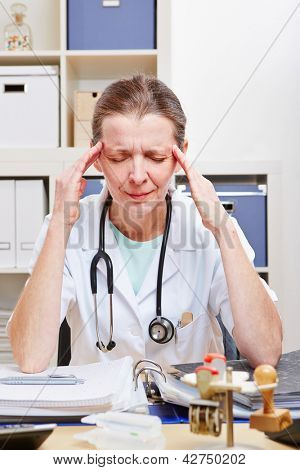 Frustrated doctor with headache in office massaging her temples