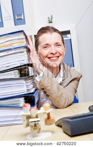 Happy elderly business woman in office with many files