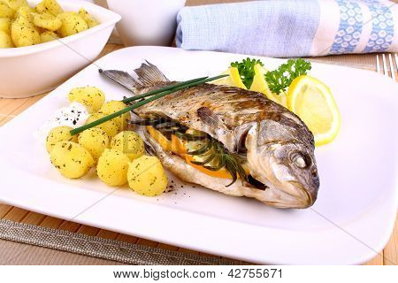 Whole Grilled Fish Served With Potatoes And Lemon