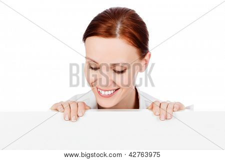 Happy smiling young business woman with a blank signboard, isolated on white background.