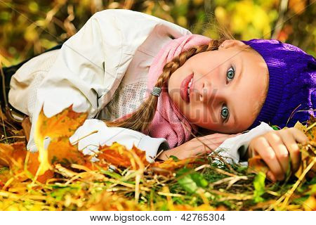 Portrait of a happy little girl lying on the leaves at the autumn park.