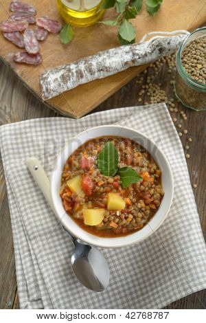 Lentil soup with sausage on a rustic table