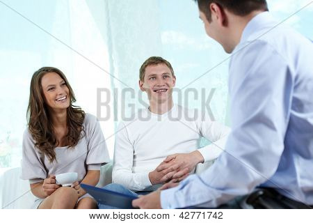 Insurance consultant or financial adviser having a friendly talk with a young couple