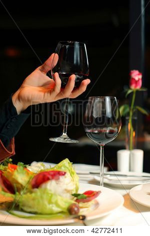 hand holds a glass of wine on a dark background. flower