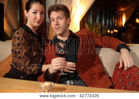 man with a glass of wine and a woman looking at the camera