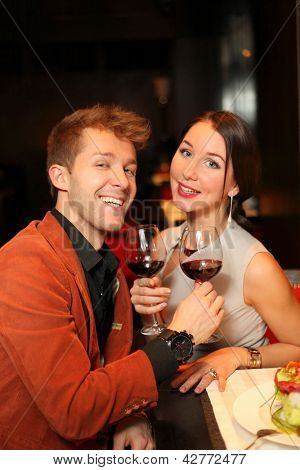 Happy man and woman with a glass of wine watching the camera