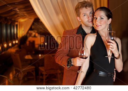 young man and woman in the restaurant for a romantic dinner, focus on woman