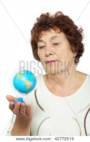 Elderly woman looks at small globe in her hand