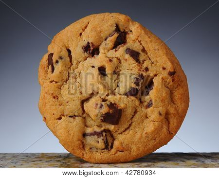 Closeup of a Chocolate Chip Cookie standing on its side on granite counter top. Light to dark gray background.