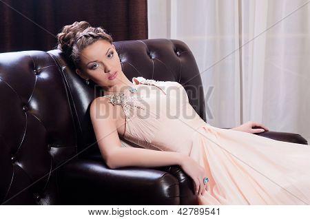 Mulher em um longo sentado no sofá