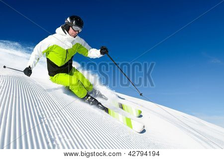 Skier in mountains, prepared piste and sunny day