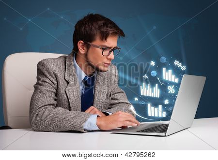 Young man sitting at desk and typing on laptop with diagrams and graphs comming out