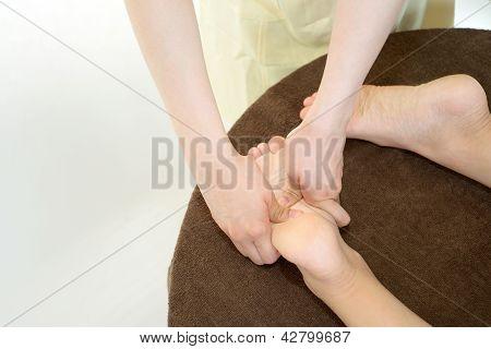 Reflexologist massaging a woman's foot