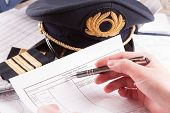 Close up of an airplane pilot hand filling in an flight plan and pre-flight checklist with equipment