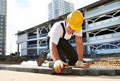 stock photo of mason  - mason worker making sidewalk pavement with stone blocks - JPG