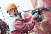 stock photo of millwright  - builders worker installing glass windows on facade of business building - JPG
