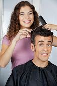 Portrait of happy hairdresser cutting client's hair at salon