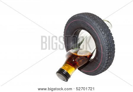 Vertical Crossed Over Vehicle Tyre And Alcohol Bottle