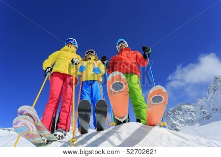Skiing, skiers, sun and fun - family enjoying winter vacation