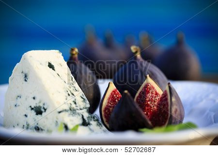 Plate of Italian delicacies, starter - figs, prosciutto, gorgonzola and rucola