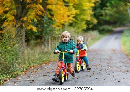 Two Little Siblings Having Fun On Bikes In Autumn Forest.