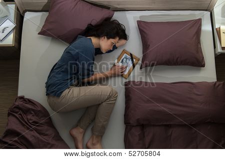 Young mourning woman lying in bed alone