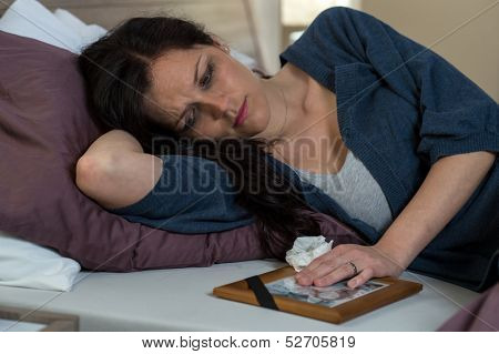 Mourning woman looking at her dead husband's photo