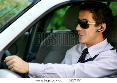 Businessman Driving In The Car With Bluetooth, Handsfree