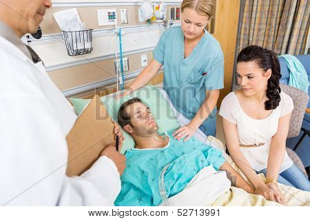 Loving woman holding patient's hand while doctor and nurse examining him in hospital