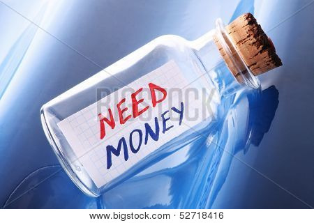 "An artistic banking concept with message in a bottle saying ""Need money"""