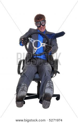 Concept Image Of A Businessman Driving Whilst Sat In An Office Chair, Isolated On A White Background