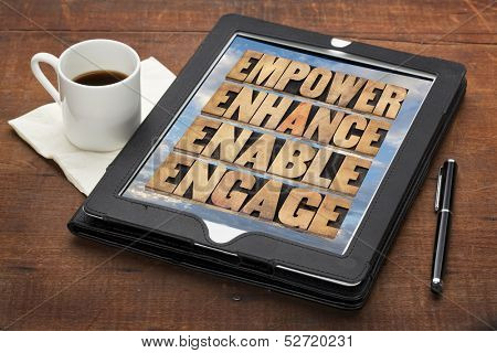 empower, enhance, enable and engage - motivational business concept - a collage of words in letterpress wood type on a digital tablet