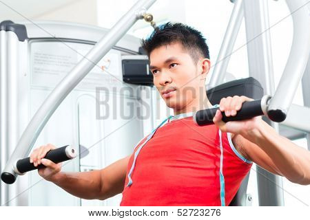 Asian Chinese man having fitness training or workout in gym doing sport to build up muscle on a weight machine