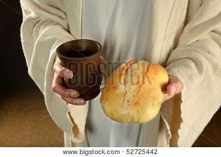 Jesus hands holding bread and wine over dark background